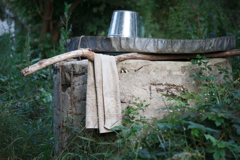 Ένας λαμπρός κενός κάδος είναι γυρισμένη άνω πλευρά - κάτω στο καπάκι καλά, μια παλαιά πετσέτα κρεμά δίπλα σε την σε ένα κλίμα θο στοκ φωτογραφίες με δικαίωμα ελεύθερης χρήσης
