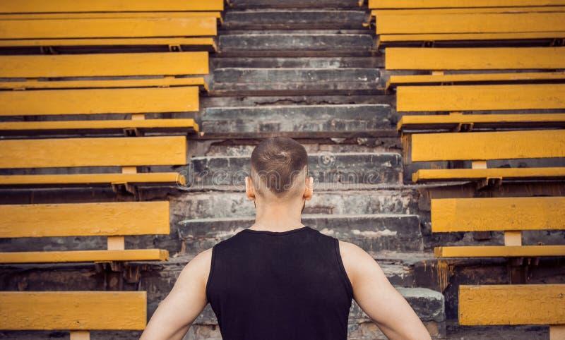Ένας λεπτός νεαρός άνδρας μαύρο sportswear στέκεται μπροστά από τις στάσεις σταδίων σκαλοπατιών έτοιμος για τη δράση, βήμα στη νί στοκ φωτογραφία με δικαίωμα ελεύθερης χρήσης
