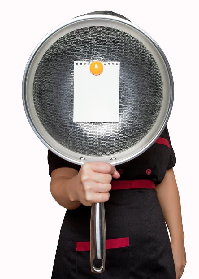 Ένας μάγειρας γυναικών κρατά ένα κενό τηγάνι μπροστά από τον με έναν κίτρινο μαγνήτη που συνδέεται με το φύλλο στοκ φωτογραφία