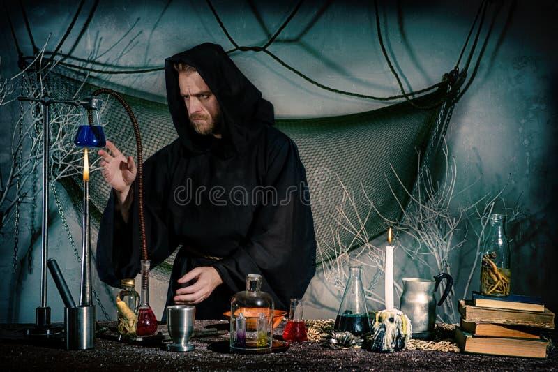 Ένας μεσαιωνικός επιστήμονας πραγματοποιεί ένα πείραμα για να λάβει μια φιλοσοφική πέτρα στοκ εικόνα