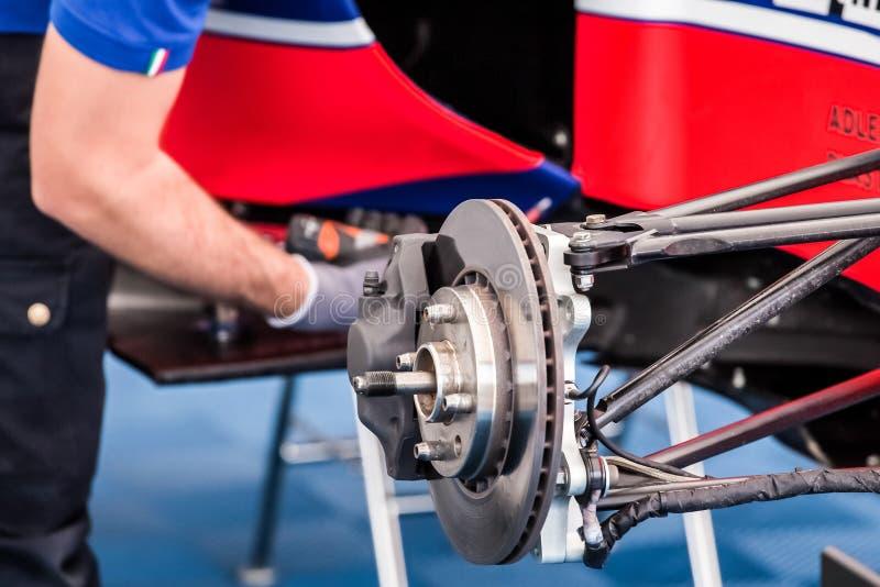 Ένας μηχανικός αναθεωρεί και επισκευάζει τη μηχανή και μερικά μηχανικά μέρη ενός supercar στοκ φωτογραφία
