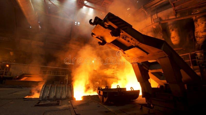 Ένας μηχανισμός με τους γάντζους στο καυτό κατάστημα με τον καπνό αύξησης και την καίγοντας πυρκαγιά στις μεταλλουργικές εγκαταστ στοκ φωτογραφία με δικαίωμα ελεύθερης χρήσης
