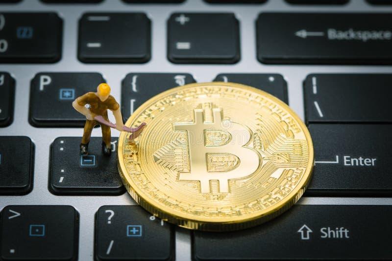 Ένας μικρός ανθρακωρύχος σκάβει για το χρυσό ψηφιακό νόμισμα bitcoin στο πληκτρολόγιο ή το lap-top χρησιμοποιώντας ως επιχείρηση  στοκ φωτογραφίες με δικαίωμα ελεύθερης χρήσης