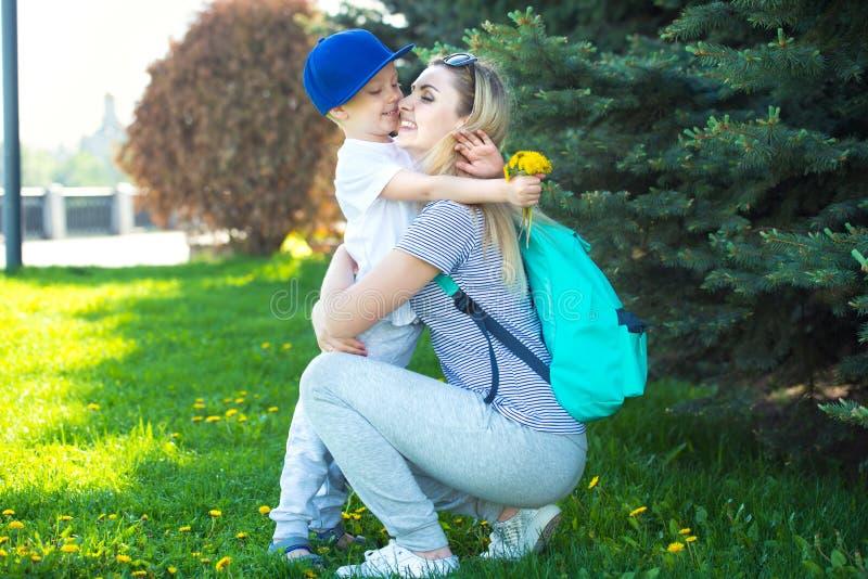 Ένας μικρός γιος δίνει στην αγαπημένη μητέρα του μια ανθοδέσμη των πικραλίδων στοκ εικόνες
