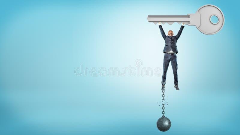 Ένας μικρός επιχειρηματίας κρατά ψηλά ένα τεράστιο κλειδί μετάλλων παίρνοντας απαλλαγμένος από μια σπασμένες σφαίρα και μια αλυσί στοκ φωτογραφίες