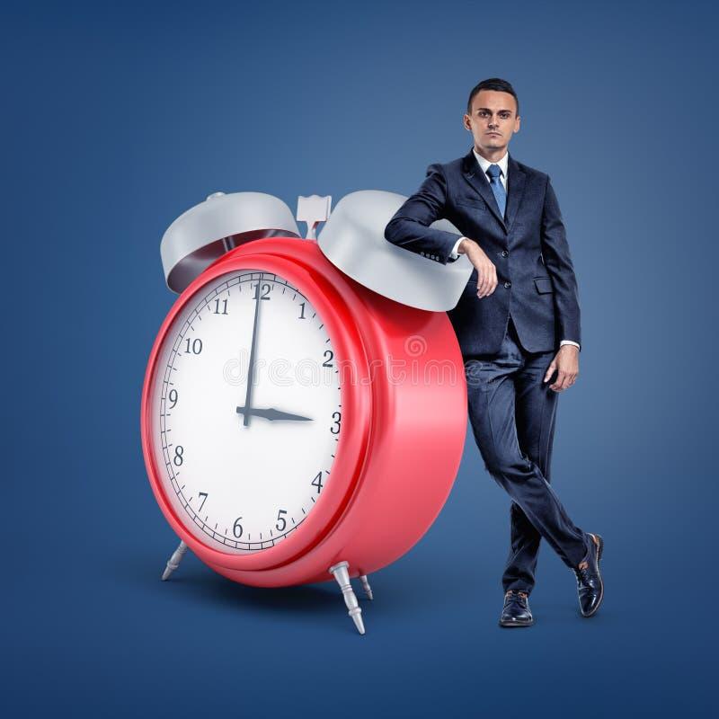 Ένας μικρός επιχειρηματίας στέκεται μπροστινό και σε ένα τεράστιο κόκκινο ξυπνητήρι στοκ εικόνες με δικαίωμα ελεύθερης χρήσης