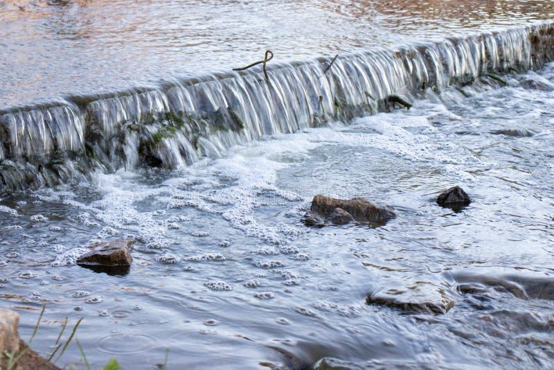 Ένας μικρός ευρύς καταρράκτης Οι πέτρες είναι ορατές από το νερό στοκ φωτογραφία με δικαίωμα ελεύθερης χρήσης