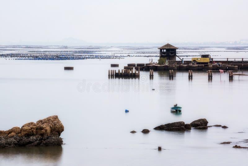 Ένας μικρός πύργος στην αλιεία της αποβάθρας με την μπλε ευθαλασσία και την αντανάκλαση του ουρανού όπως τον καθρέφτη, μακρύς πυρ στοκ εικόνα με δικαίωμα ελεύθερης χρήσης