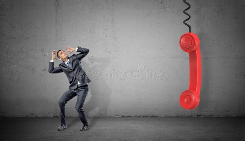 Ένας μικρός φοβησμένος επιχειρηματίας στο συγκεκριμένο υπόβαθρο κοντά σε μια μεγάλη κόκκινη αναδρομική τηλεφωνική λαβή που κρεμά  στοκ εικόνα