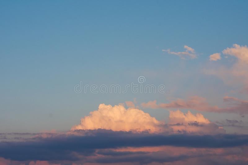 Ένας μπλε νεφελώδης ουρανός Η αντανάκλαση των κίτρινων ακτίνων ήλιων στο clou στοκ φωτογραφία με δικαίωμα ελεύθερης χρήσης