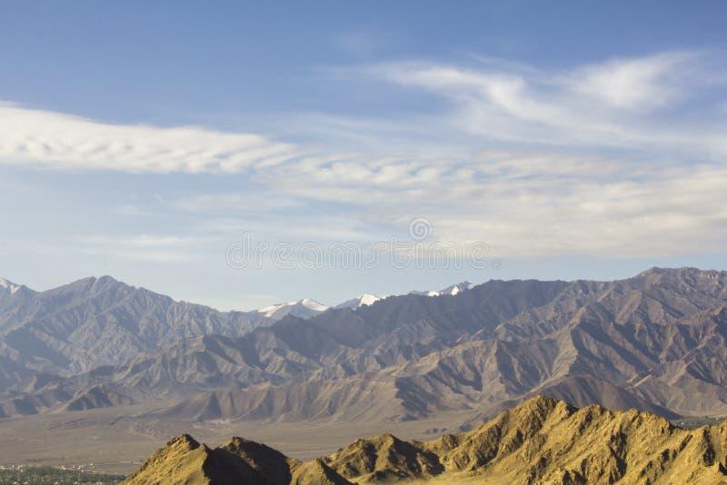 Ένας μπλε ουρανός με τα άσπρα σύννεφα επάνω από μια κοιλάδα βουνών ερήμων με τις χιονώδεις αιχμές Ιμαλάια Ινδία Ladakh στοκ εικόνα