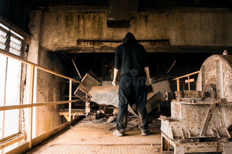 Ένας μυστήριος με κουκούλα αριθμός από πίσω, κοιτάζοντας κάτω στο μη χρησιμοποιούμενο εξοπλισμό σε ένα εγκαταλειμμένο βιομηχανικό στοκ εικόνες