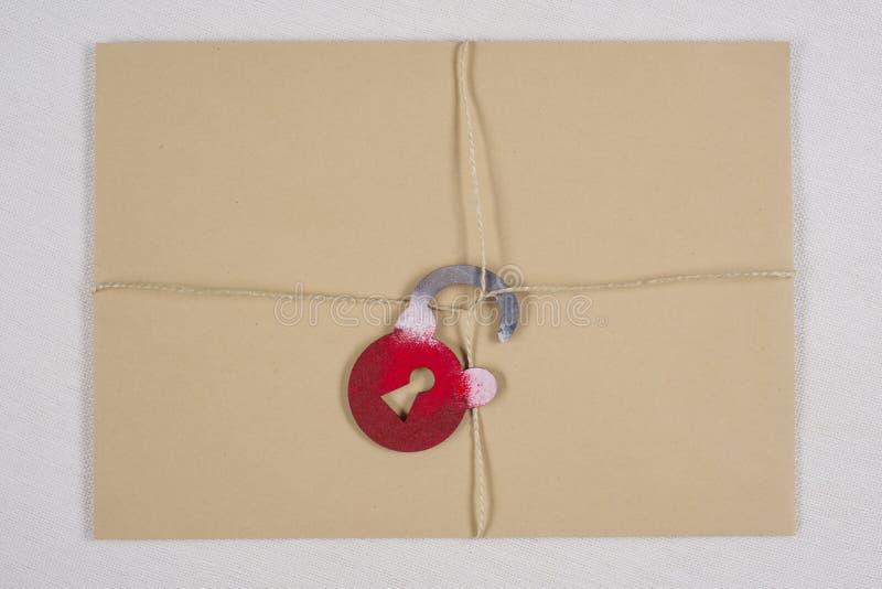 Ένας μυστικός φάκελος, ένα δέμα δέσμευσε με ένα σχοινί, με τη συμβολική κλειδαριά κλείδωμα ανοικτό στοκ φωτογραφία με δικαίωμα ελεύθερης χρήσης