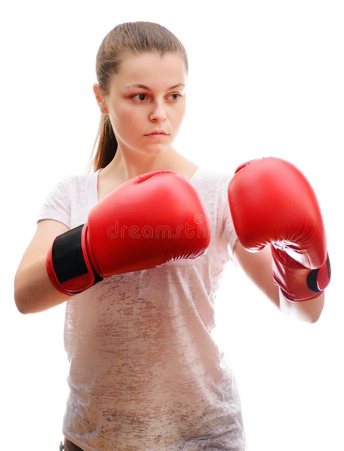 Ένας νέος αθλητικός γυναίκα-μπόξερ θέτει στη κάμερα στα κόκκινα εγκιβωτίζοντας γάντια Συγκεντρώνεται και στεμένος στο ράφι μάχης στοκ φωτογραφίες