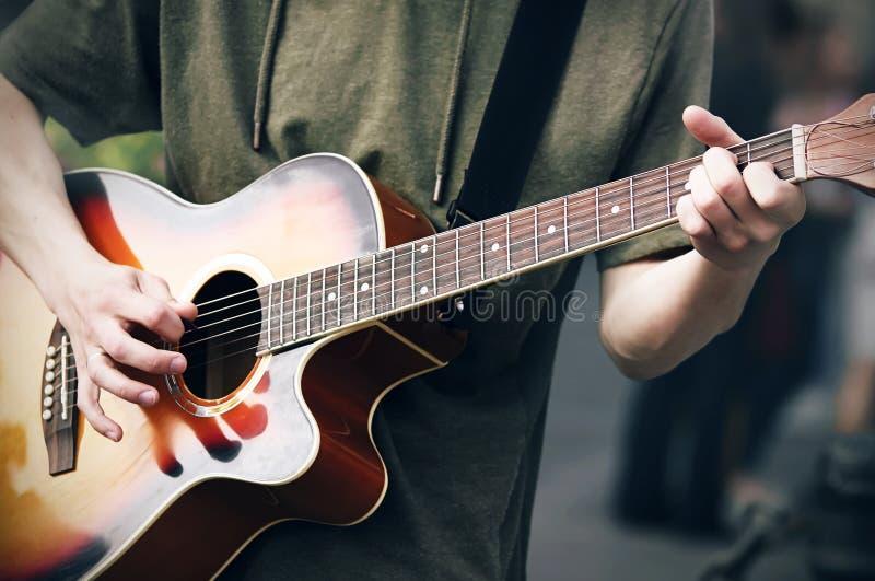 Ένας νέος αναιδής τύπος σε ένα πράσινο hoodie παίζει μια φωτεινή χρωματισμένη ακουστική κιθάρα έξι-σειράς στοκ εικόνα με δικαίωμα ελεύθερης χρήσης