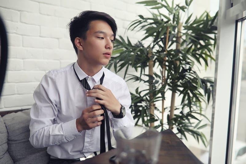 Ένας νέος ασιατικός επιχειρηματίας περιμένει έναν συνεργάτη σε έναν καφέ Bu στοκ φωτογραφία με δικαίωμα ελεύθερης χρήσης