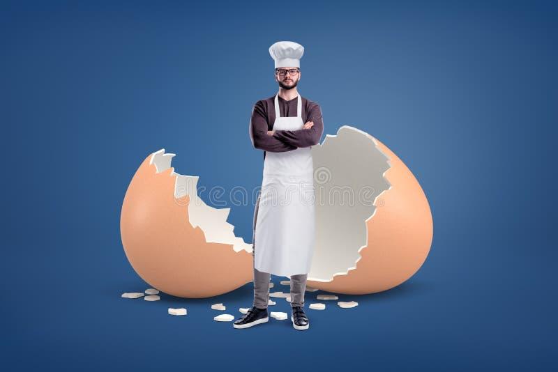 Ένας νέος γενειοφόρος μάγειρας σε μια άσπρη ποδιά και ένα καπέλο στέκεται κοντά σε ένα μεγάλο σπασμένο κοχύλι αυγών στοκ εικόνα με δικαίωμα ελεύθερης χρήσης