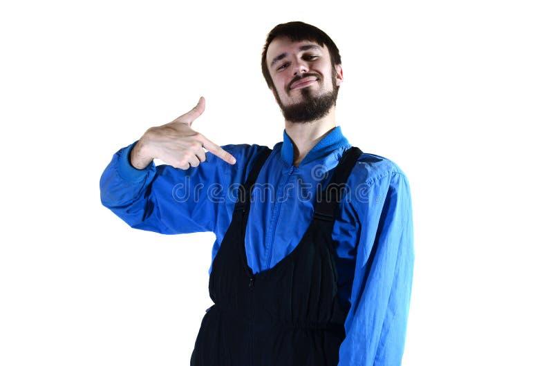 Ένας νέος γενειοφόρος τύπος στα λειτουργώντας ομοιόμορφα σημεία σε τον με το δάχτυλό του στοκ εικόνα