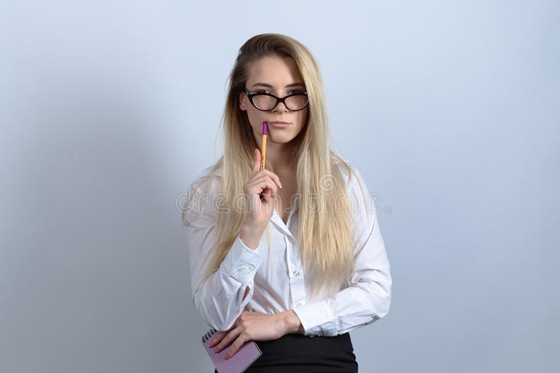 Ένας νέος εκπαιδευόμενος δημοσιογράφος οικότροφων σπουδαστών γυναικών στα γυαλιά και ένα β στοκ εικόνα