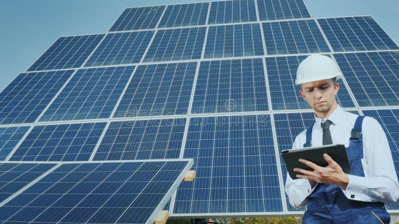 Ένας νέος επιχειρηματίας σε ένα άσπρο κράνος χρησιμοποιεί μια ταμπλέτα στο υπόβαθρο των ηλιακών πλαισίων στοκ εικόνες
