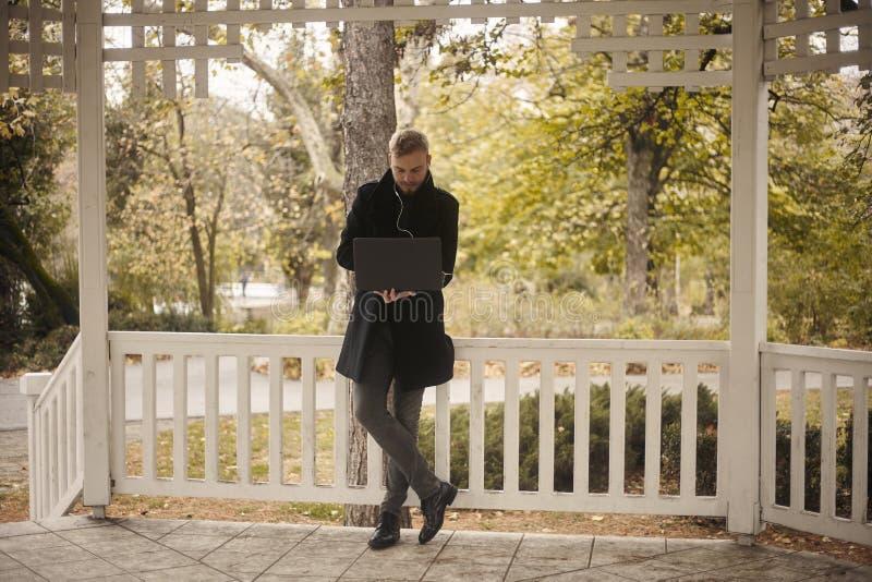 Ένας νέος επιχειρηματίας, 20-29 χρονών, επιχειρηματίας, που κρατά το lap-top διαθέσιμο, άνετα που απασχολείται δημόσια στο πάρκο  στοκ εικόνες