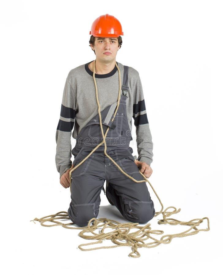 Ένας νέος εργαζόμενος γκρίζο σε ομοιόμορφο που σχετίζεται με το σχοινί απομονωμένο στο λευκό υπόβαθρο στοκ φωτογραφίες με δικαίωμα ελεύθερης χρήσης