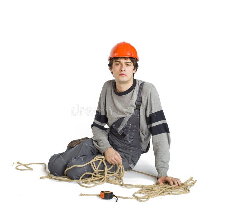 Ένας νέος εργαζόμενος γκρίζο σε ομοιόμορφο που σχετίζεται με το σχοινί απομονωμένο στο λευκό υπόβαθρο στοκ εικόνες