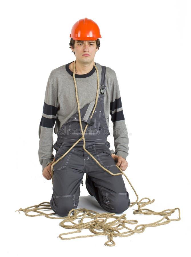 Ένας νέος εργαζόμενος γκρίζο σε ομοιόμορφο που σχετίζεται με το σχοινί απομονωμένο στο λευκό υπόβαθρο στοκ φωτογραφίες