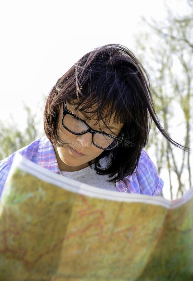 Ένας νέος θηλυκός τουρίστας που εξετάζει το χάρτη στοκ εικόνες με δικαίωμα ελεύθερης χρήσης