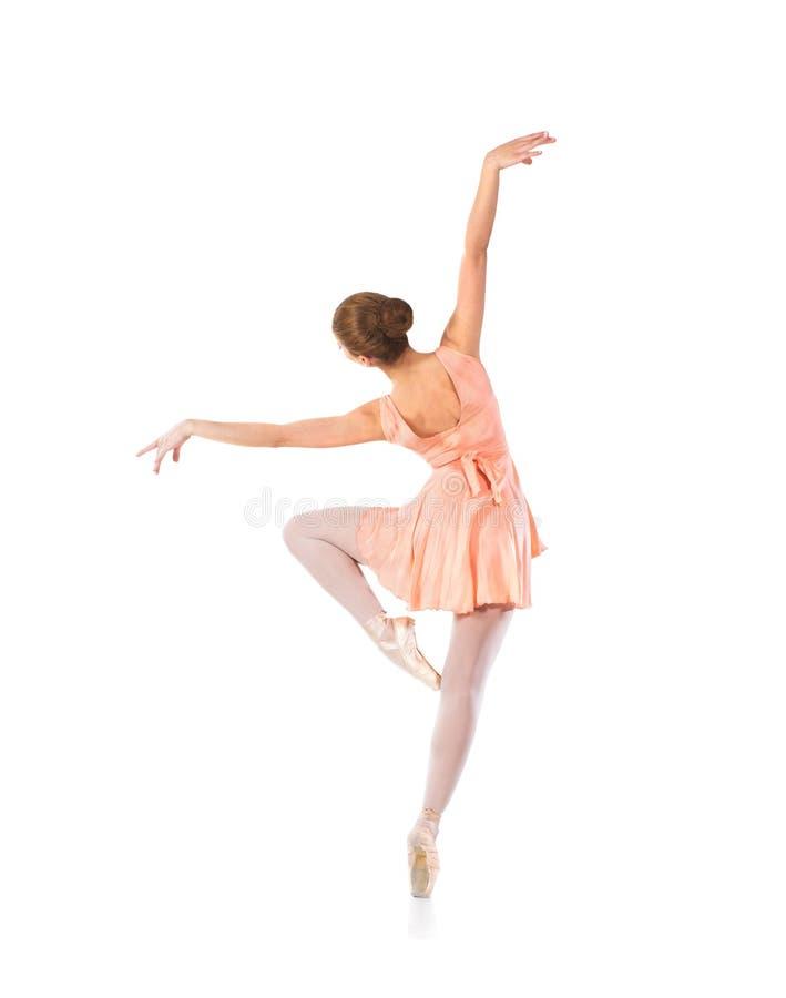 Ένας νέος και κατάλληλος θηλυκός χορευτής μπαλέτου σε ένα πορτοκαλί φόρεμα στοκ εικόνα