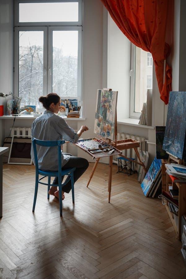 Ένας νέος καλλιτέχνης γυναικών στο στούντιο στοκ εικόνες