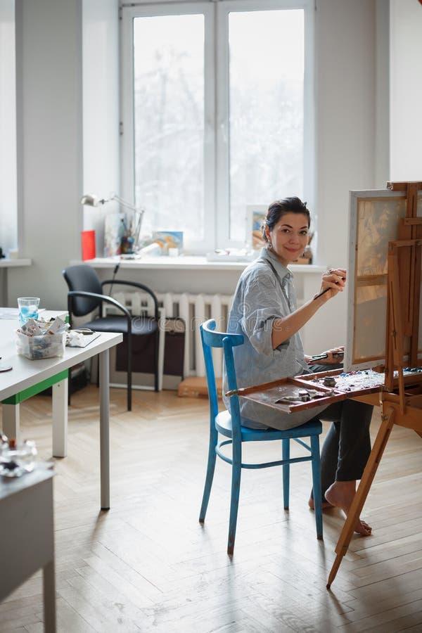 Ένας νέος καλλιτέχνης γυναικών χρωματίζει μια ελαιογραφία easel στοκ εικόνα