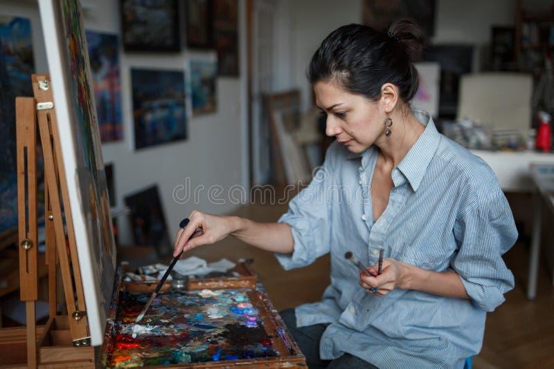 Ένας νέος καλλιτέχνης γυναικών χρωματίζει μια ελαιογραφία easel στοκ εικόνες