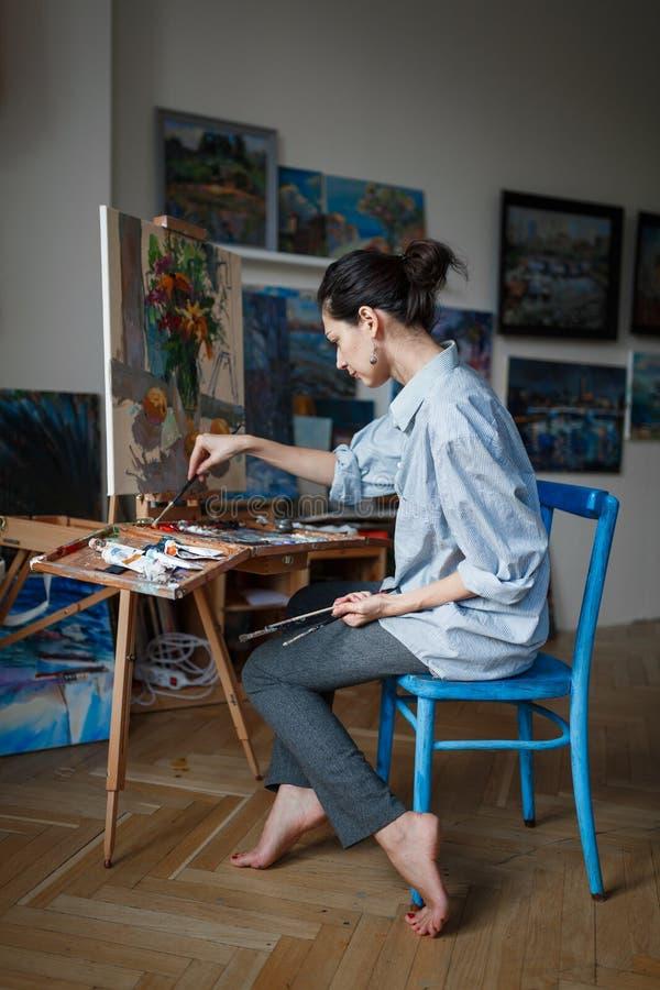 Ένας νέος καλλιτέχνης γυναικών χρωματίζει μια ελαιογραφία easel στοκ φωτογραφίες
