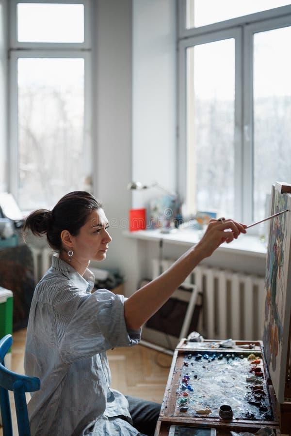 Ένας νέος καλλιτέχνης γυναικών χρωματίζει μια ελαιογραφία easel στοκ εικόνες με δικαίωμα ελεύθερης χρήσης