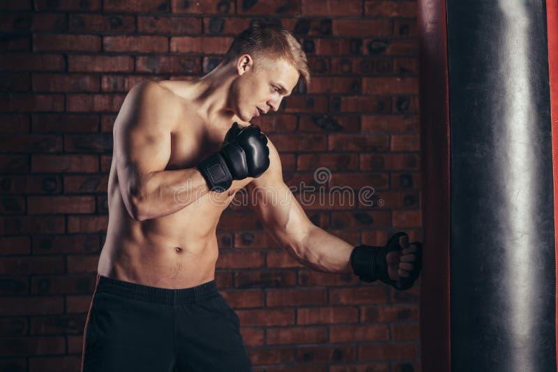 Ένας νέος μπόξερ στα μαύρα γάντια με έναν γυμνό κορμό επιλύει τις απεργίες punching στην τσάντα στοκ φωτογραφία
