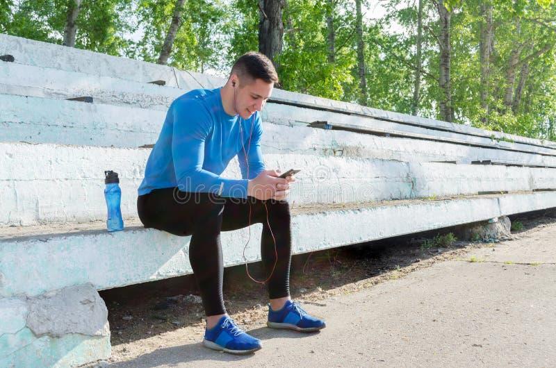 Ένας νέος μυϊκός αθλητικός τύπος κάθεται στις στάσεις και ακούει τη μουσική μετά από να εκπαιδεύσει στοκ εικόνες με δικαίωμα ελεύθερης χρήσης