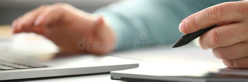 Ένας νέος σχεδιαστής κρατά μια μάνδρα από μια ταμπλέτα σε δικοί του στοκ φωτογραφία