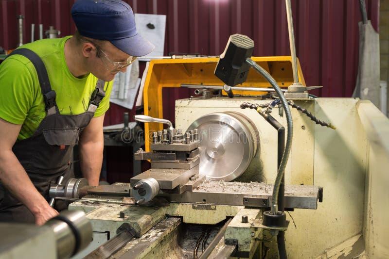 Ένας νέος τορναδόρος επεξεργάζεται ένα κομμάτι προς κατεργασία μετάλλων σε έναν μηχανικό τόρνο στοκ εικόνα με δικαίωμα ελεύθερης χρήσης