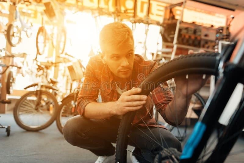 Ένας νέος τύπος εξετάζει μια ρόδα από ένα ποδήλατο στοκ εικόνα