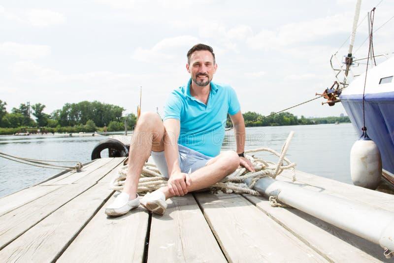 Ένας νέος τύπος κάθεται στο μπλε πόλο στην αποβάθρα κοντά στο γιοτ ευτυχές χαμογελασμένο όμορφο άτομο τουριστών που χαλαρώνει και στοκ φωτογραφία