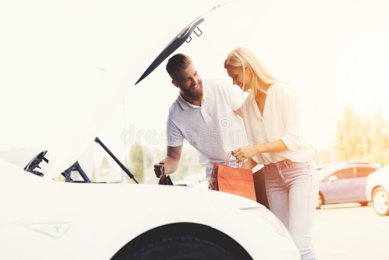 Ένας νέος τύπος και ένα κορίτσι βάζουν τις αποσκευές στον κορμό του ηλεκτρικού αυτοκινήτου τους στοκ φωτογραφία με δικαίωμα ελεύθερης χρήσης