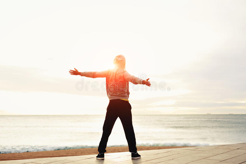 Ένας νέος τύπος με τα όπλα του στην παραλία που στέκεται δίπλα στη θάλασσα στοκ εικόνα με δικαίωμα ελεύθερης χρήσης