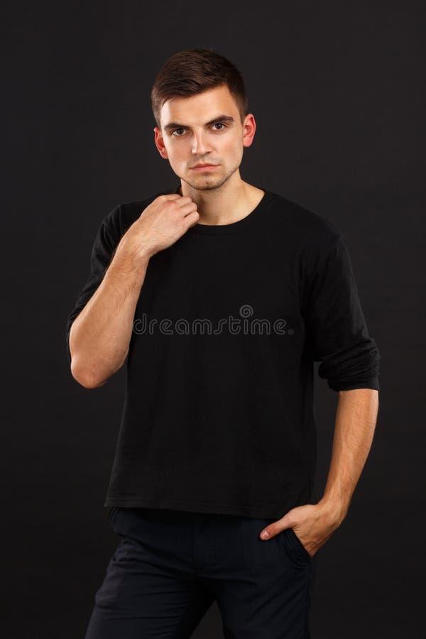 Ένας νέος τύπος με τη σκοτεινή τρίχα θέτει σε ένα μαύρο υπόβαθρο, ραβδιά ενός χεριού στο περιλαίμιο indoors στοκ φωτογραφία με δικαίωμα ελεύθερης χρήσης