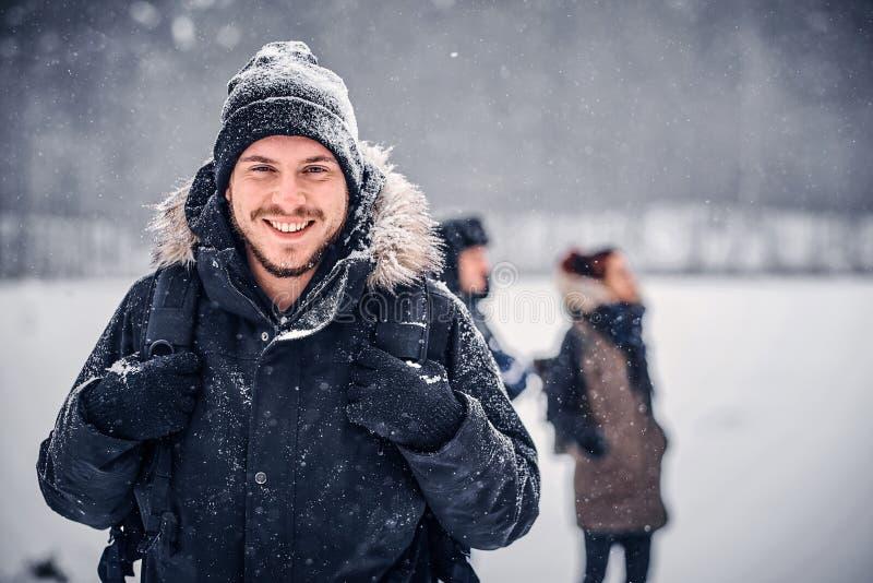 Ένας νέος τύπος οδοιπόρων με ένα σακίδιο πλάτης που περπατά με τους φίλους του μέσω των ξύλων ενός χειμώνα στοκ φωτογραφίες με δικαίωμα ελεύθερης χρήσης