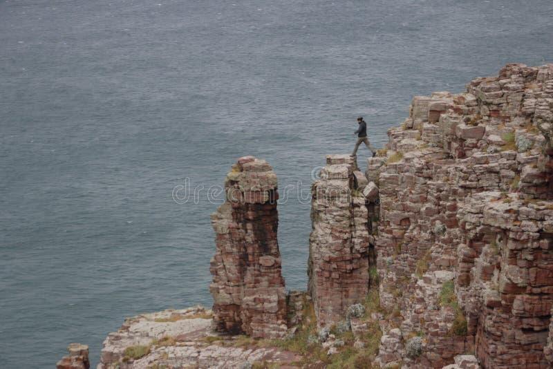 Ένας νέος τύπος ορειβατών βράχου πηδά πέρα από τους βράχους ενάντια στο σκηνικό της θάλασσας στοκ εικόνα
