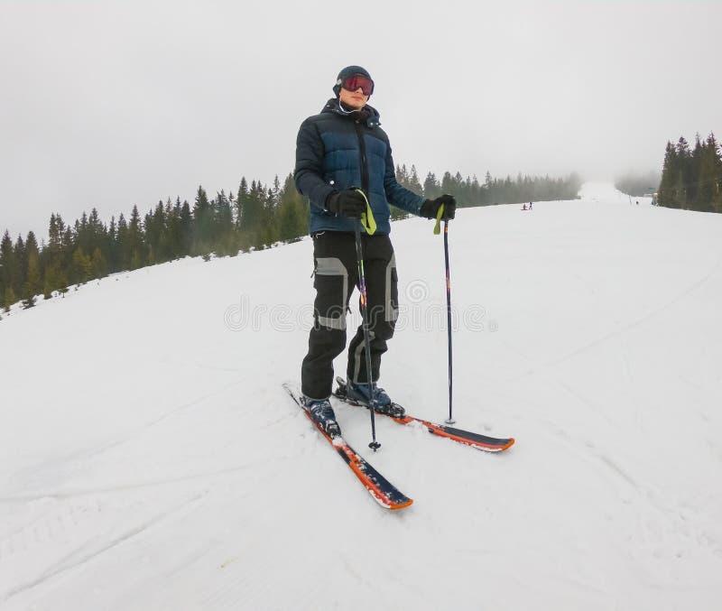 Ένας νέος τύπος στα αθλητικά γυαλιά και να κάνει σκι στα βουνά μέσα στοκ εικόνες