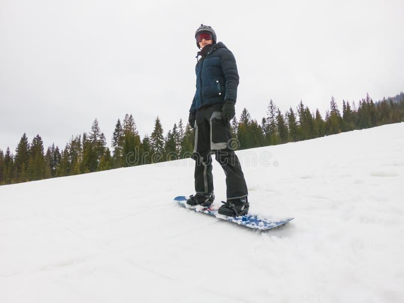 Ένας νέος τύπος στα αθλητικά γυαλιά οδηγά ένα σνόουμπορντ στο υποστήριγμα στοκ φωτογραφία με δικαίωμα ελεύθερης χρήσης