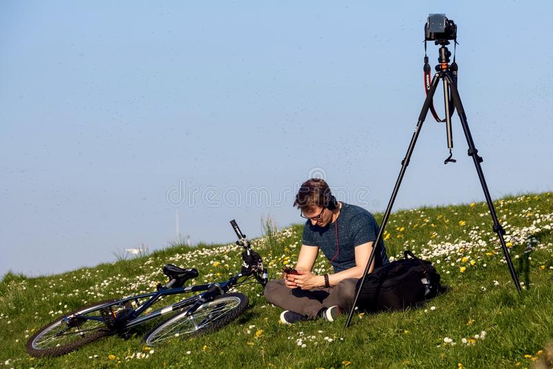 Ένας νέος φωτογράφος που περιμένει το ηλιοβασίλεμα στοκ φωτογραφία