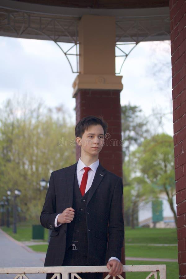 Ένας νεαρός άνδρας, ένας έφηβος, σε ένα κλασικό κοστούμι Σκέφτηκε για το, που κλίνει το χέρι του στο κιγκλίδωμα του περίπτερου πε στοκ εικόνα με δικαίωμα ελεύθερης χρήσης
